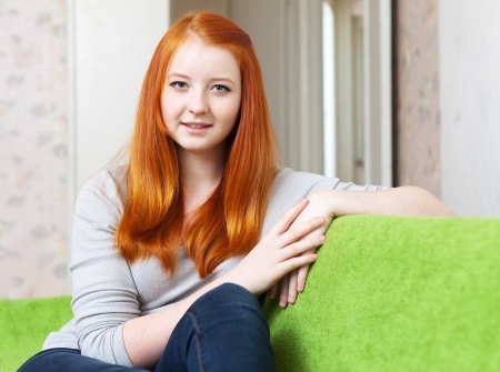 tenager:  ordinary red-haired tenager girl in home interior  Stock Photo