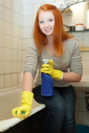 Teenager cleans mirror with sponge in bathroom at home   photo