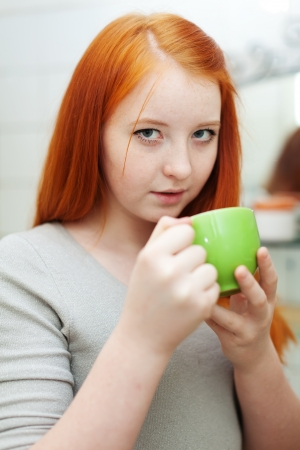 red-haired teen girl gargling throat in her bathroom at home photo