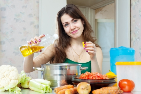woman cooking: beautiful housewife cook vegetables with oil at her kitchen at home