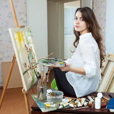 Female artist paints picture on canvas with oil paints in her stidio photo