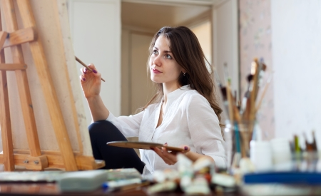 painting:  woman paints picture on canvas with oil paints in her studio