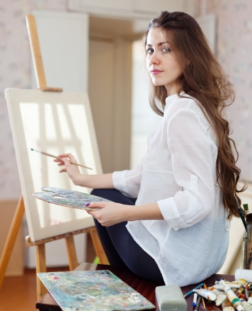Long-haired woman with oil colors and brushes near easel with blank canvas ready for job  in workshop photo