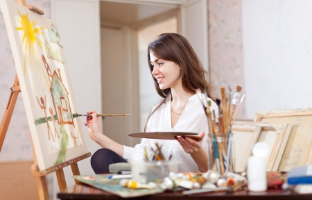 Happy young woman paints landscape on canvas in workshop photo