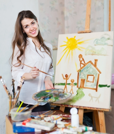 Happy young woman paints home  in workshop photo