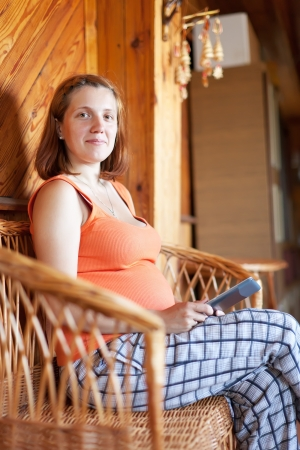 pregnant woman reads e-book in home interior Stock Photo - 18345981