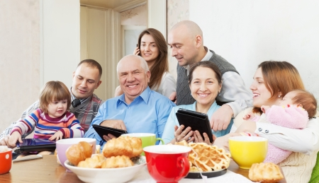 multigeneration: Portrait of happy multigeneration family uses electronic devices over tea
