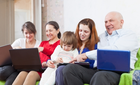 Happy family uses few electronic devices together photo