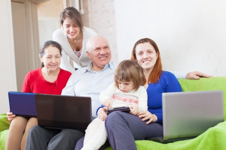 Happy multigeneration family uses few various portable devices in home interior   photo