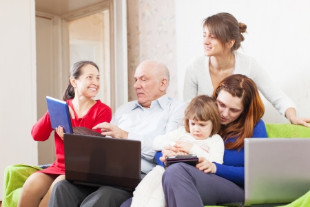 Happy family enjoys in livingroom room with few laptops at home Stock Photo - 18359690
