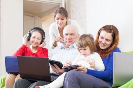 Familia multigeneracional feliz junto con algunos dispositivos electrónicos de comunicación en el hogar