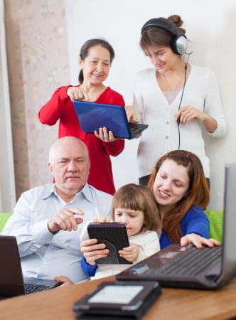 few: Happy multigeneration family uses few various electronic devices in home Stock Photo