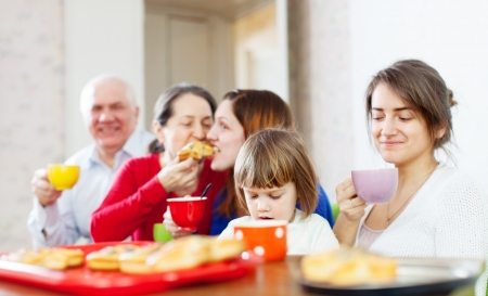 family having tea with cakes at home together photo