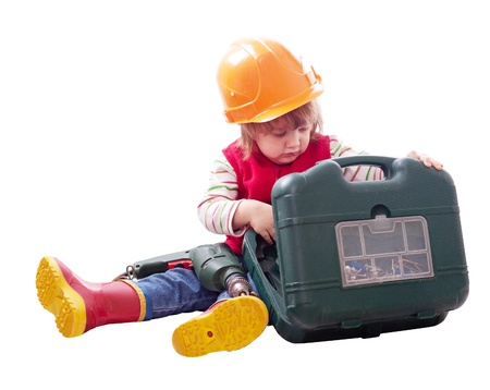 2 years child in hardhat chooses tools in toolbox. Isolated over white background  photo