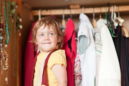Baby girl looking at clothes in a closet photo