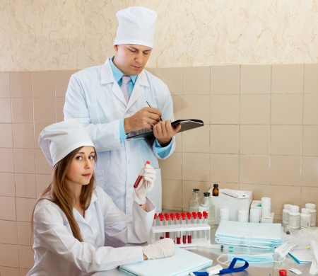 Male doctor supervises the young nurse in medical lab Stock Photo - 18417180