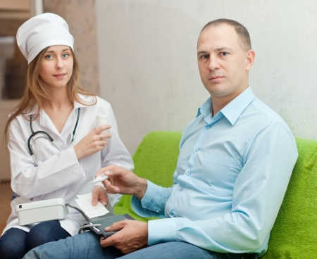 Woman doctor examining the patient in home. Focus on man Stock Photo - 18417172