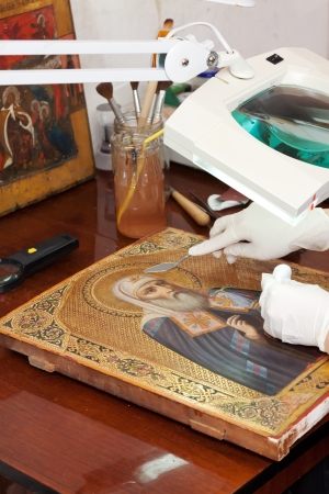 Closeup of accurate restoration of old icon with  filling knife at workshop photo