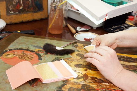 gilding:  gilding of ancient icon with leaf-gold in workshop