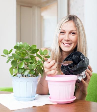 replant: Donna sorridente di trapianti Kalanchoe pianta in vaso di fiori a casa sua Archivio Fotografico
