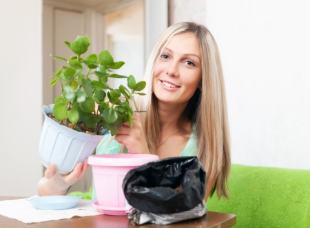 Happy young woman transplants  Kalanchoe flower in flowerpot at her home photo