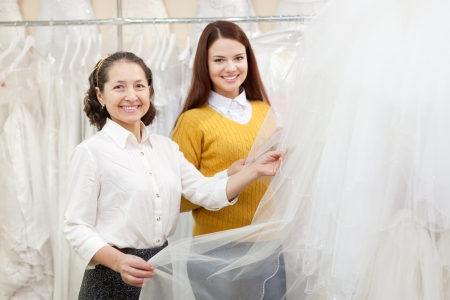 Woman helps the bride in choosing bridal veil at shop of wedding fashion. Focus on mature Stock Photo - 18493265