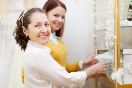 women  chooses bridal accessories in wedding boutique photo