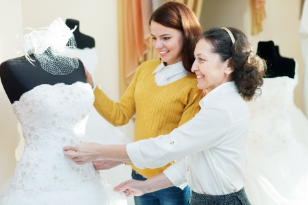 bridal gown: mother  with daughter chooses bridal gown at shop of wedding fashion. Focus on mature