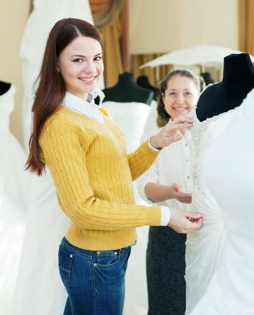bridal gown: Dos mujeres felices elige vestido de novia en la boutique de boda