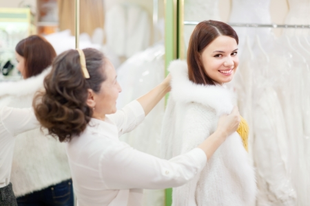 furskin: Mature woman with girl chooses white fur cape at shop of wedding fashion. Focus on young bride