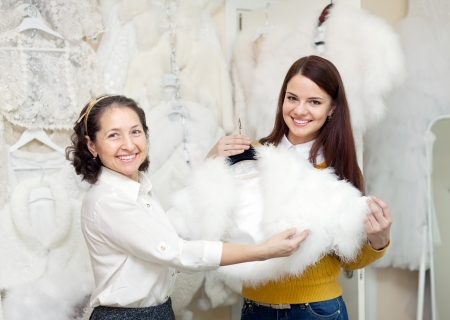 furskin: happy women chooses bridal outfit at wedding store. Focus on young bride  Stock Photo