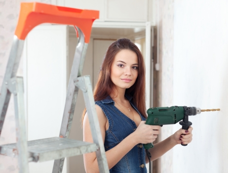 Beautiful  woman in overalls with drill makes repairs in the apartment photo