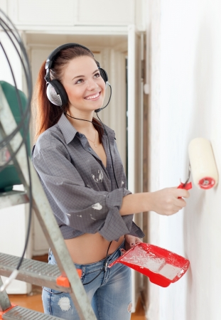 Happy young girl in headphones paints wall with roller at home photo