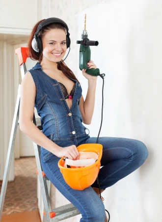 Sexy beauty woman in headphones with drill and hardhat on staircase in interior photo