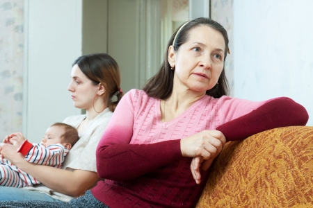 fracas: Sad mature woman against adult daughter with baby having conflict at home. Focus on grandmother