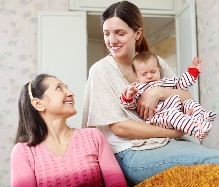 happy mature woman talking to her adult daughter with granddaughter at home interior Stock Photo - 18498223