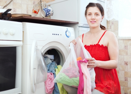 woman in red uses bag for laundry in washing machine  photo