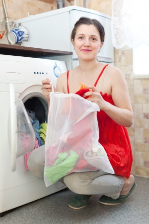 Woman in red loading the washing machine at her home Stock Photo - 18498228