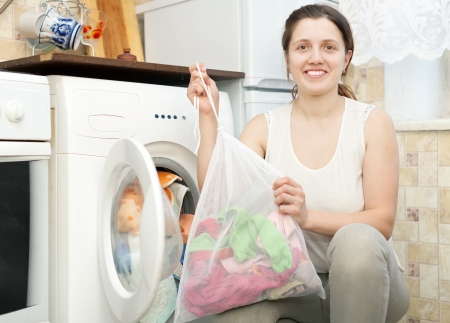 Young smiling housewife loading the washing machine with laundry bag in kitchen photo