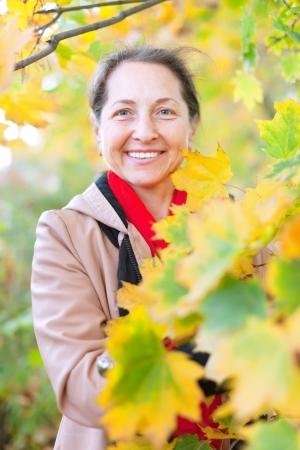 happy seasonable: Portrait of happy mature woman  in autumn park Stock Photo