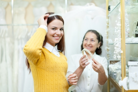 Mature saleswoman helps bride chooses bridal diadem at shop of wedding fashion photo