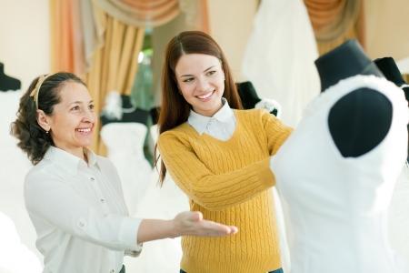 bridal gown: Vendedora mayor ayuda a la novia elige vestido de novia en la tienda de moda nupcial
