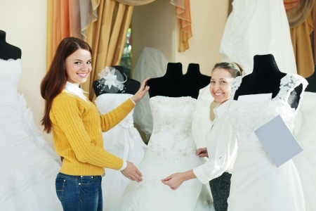 woman helps girl chooses white bridal outfit at shop of wedding fashion Stock Photo - 18559107