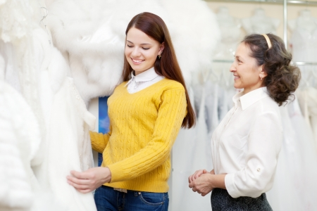 furskin: Girl chooses  bridal clothes at shop of wedding fashion. Friendly shop consultant helps her