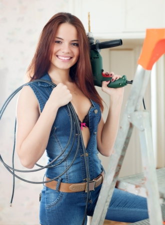 Sexy girl in dungarees with drill and cable on stepladder in interior photo