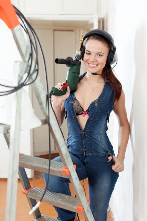 smiling sexy  girl in headphones with drill  near stepladder in interior photo