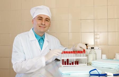 tourniquet: Male nurse with test tubes makes haemanalysis
