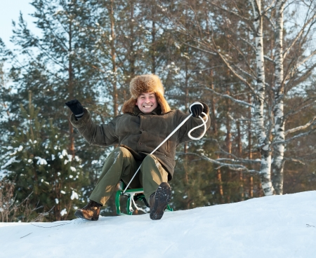 vacaton: Man doing downhill on sleigh in winter