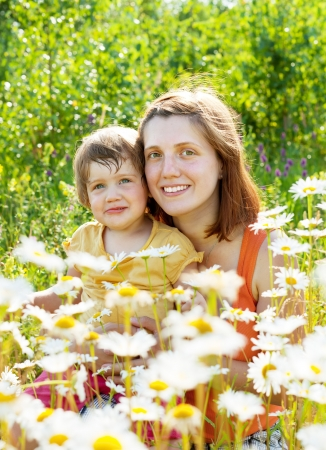 Happy mother with daughter in summer camomile plant Stock Photo - 18578130