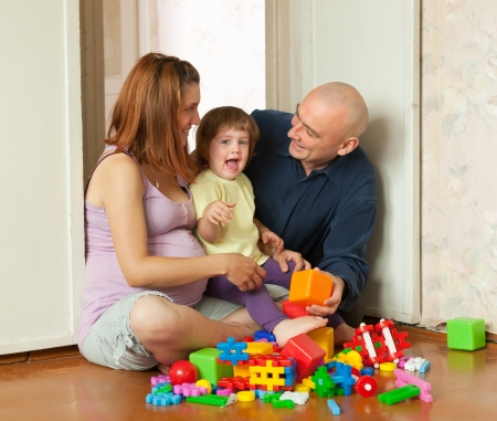 Happy family plays in home interior photo